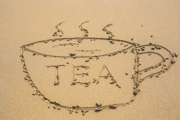 cup of tea drawn on sand and word tea written on a beach
