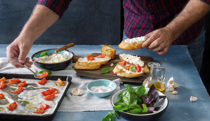 Man preparing an Italian bruschetta with baked tomatoes, basil, cheese