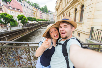 Happy romantic couple of tourists makes selfie self-portrait in Karlovy Vary while traveling across Europe.
