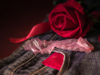 Low key of condom and red rose on pink background. Save sex , Family plan  and Valentine concept.