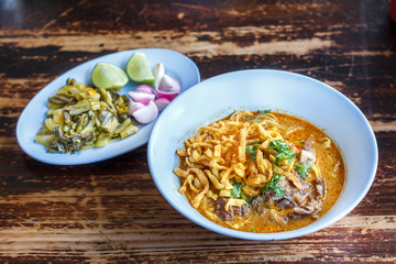 Curried noodle soup (Khao soi) with chicken meat and spicy coconut milk on wood table. Thai food cuisine northern style in Chiang Mai, Thailand.