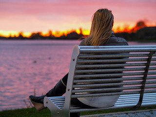 blonde girl on bench enjoying sunset