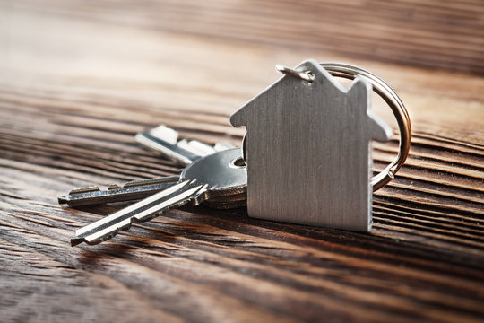 estate concept with symbol of house, key on wooden background