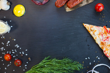 Background. Black slate with pizza, vegetables, food spice and herbs