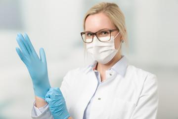 Junge hübsche Ärztin mit Mundschutz zieht Handschuhe an