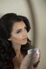 Woman has long hair drink tea or coffee from cup