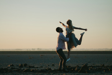 Man and a balerina dancing on the beach