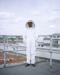 A bee Keeper stands among the rooftops of central London