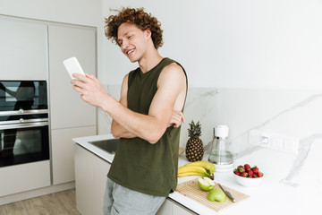 Man standing at the kitchen and chatting by phone