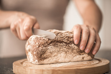 fresh bread in hands closeup on old wooden background
