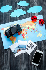 children tourism outfit with mobile, map and pictures on dark background flat lay mockup