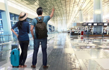 Excited asian couple traveler pointing with hand