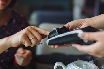 Woman paying his bill in restaurant, using credit card