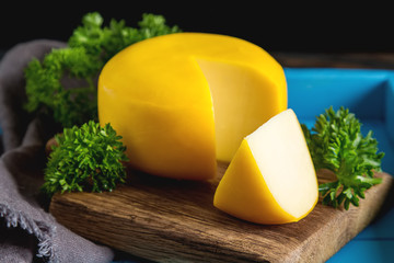 Round gouda cheese with parsley. Dark background.