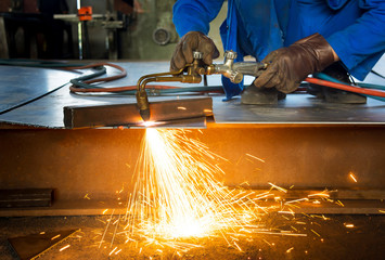Man cutting metal with a welding cutting torch