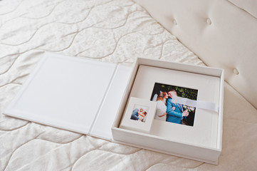 Gorgeous white leather wedding photobooks or photo albums in the box on the white background.