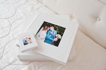 Elegant wedding photobooks or photo albums on the white bed background.