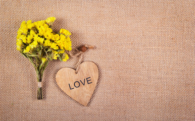 A bouquet of yellow wildflowers and a wooden heart on a natural linen background. Romantic concept. Backgrounds and textures. Copy space