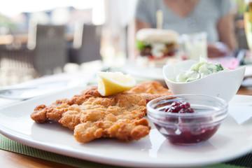 Wiener Schnitzel klassisch im Biergarten mit Gurkensalat und Preiseilbeeren
