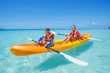 Two chirdren kayaking at tropical sea on yellow kayak