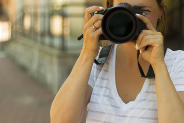 Portrait of a photographer covering her face with the camera.. Photographer woman girl is holding dslr camera taking photographs. Focus on a woman's face
