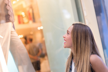 Pretty girl watching a fashion shop window. Fashion, lifestyle and retail concepts.
