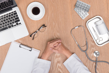 Top view of adult doctor working with clipboard on his desk and holding pen