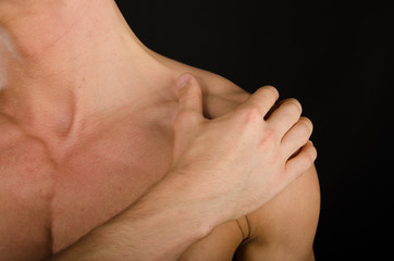 Pain in the neck. Attractive guy. Black background.