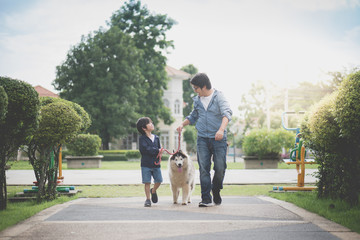 father and son walking with a siberian husky don in the park
