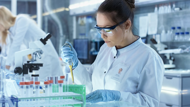 Female Research Scientist Uses Micropipette Filling Test Tubes in a Big Modern Laboratory. In the Background Scientists are Working.