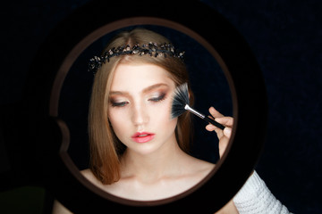 ring with a constant light for illuminating makeup Shine to the girl model for a beauty photo shoot. She makes a correction of the cheekbones
