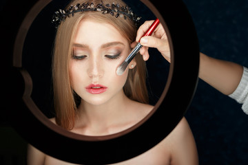 ring with a constant light for illuminating makeup Shine to the girl model for the beauty photo shoot. She makes The correction of the cheekbones