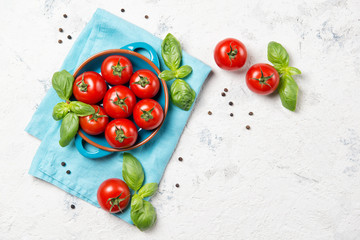 Fresh cherry tomatoes in a bowl, basil leaves and black pepper on stone table, closeup, top view with copy space