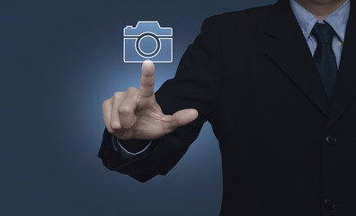 Businessman pressing camera flat icon over gradient blue background, Business camera service concept