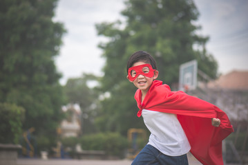 Asian child in in Superhero's costume playing