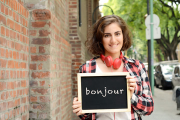 "Woman holding chalkboard with ""bonjour""."