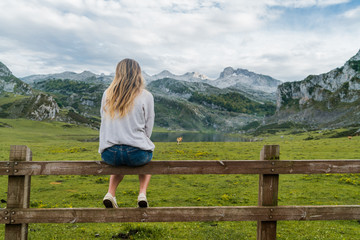 Woman sitting at mountain pasture