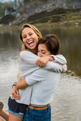 Girls hugging at lake