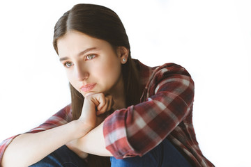 portrait of depressed teen girl sitting and crying isolated on white