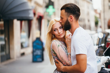 Blonde girl and Hipster handsome man with beard hugging and kissing on the city streets