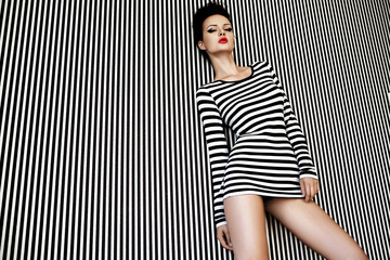 fashion woman in striped dress on  background.