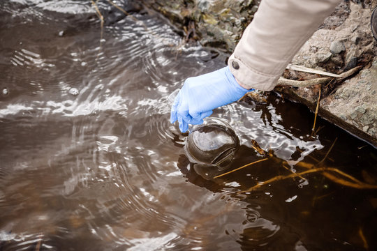 hand in glove collects water sample to explore and testing for infections. water and ecology concept.