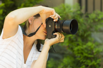 Attractive young woman photographer taking photos with dslr camera outdoors. Copy space