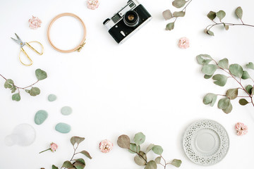 Flat lay border frame with retro camera, eucalyptus branches, plate and scissors on white background. Top view artist background with space for text.