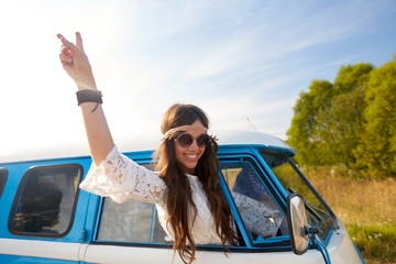 happy hippie woman showing peace in minivan car