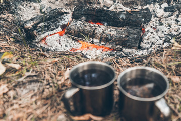 two metal cups with tea near bonfire