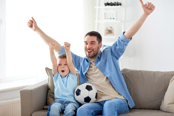 father and son watching soccer on tv at home