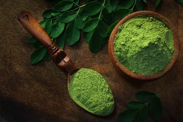 Overhead view of Moringa powder in an earthern pot on dark wooden background
