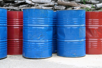 Empty tank of 200 liter fuel. blue and red color Put in front of old wood pile.