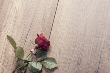 Retro style image of a red rose with engagement ring around it